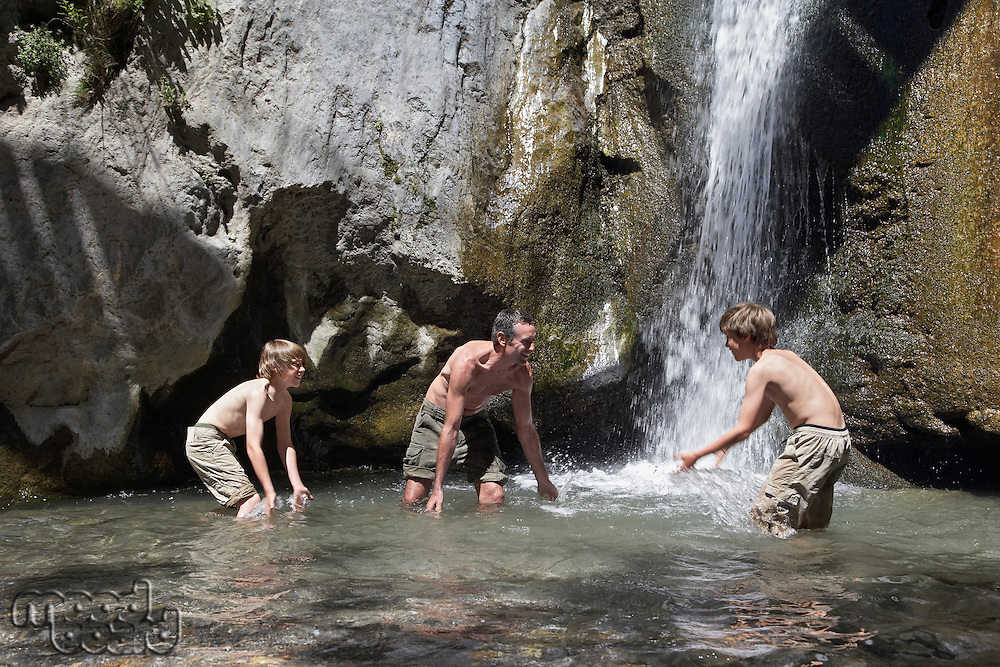 Father with two sons (7-12) splashing in river