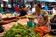 A woman wearing a head scarf shopping in the market in Mahebourg, Mauritius, The Indian Ocean