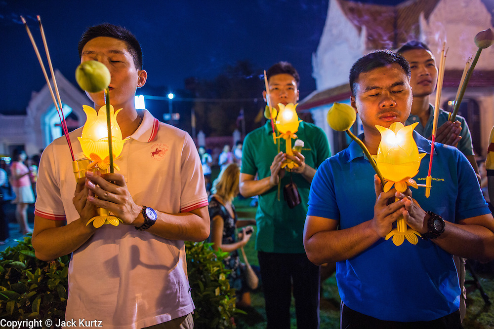 "25 FEBRUARY 2013 - BANGKOK, THAILAND:  Thai men pray in front of Wat Benchamabophit Dusitvanaram (popularly known as either Wat Bencha or the Marble Temple) on Makha Bucha Day. Thais visit temples throughout the Kingdom on Makha Bucha Day to make merit and participate in candle light processions around the temples. Makha Bucha is a Buddhist holiday celebrated in Myanmar (Burma), Thailand, Cambodia and Laos on the full moon day of the third lunar month (February 25 in 2013). The third lunar month is known in Thai is Makha. Bucha is a Thai word meaning ""to venerate"" or ""to honor"". Makha Bucha Day is for the veneration of Buddha and his teachings on the full moon day of the third lunar month. Makha Bucha Day marks the day that 1,250 Arahata spontaneously came to see the Buddha. The Buddha in turn laid down the principles his teachings. In Thailand, this teaching has been dubbed the 'Heart of Buddhism'.     PHOTO BY JACK KURTZ"