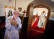 NORTH LAKE, WI — JANUARY 18, 2015:  Reverend David Couper prepares for mass as junior warden Peter Buerosse rings the bells at the St. Peter's Episcopal Church, Sunday, January 18, 2015. <br />