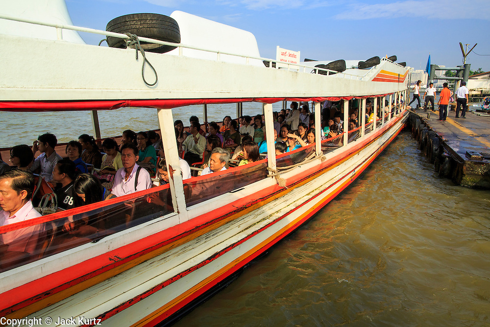 21 NOVEMBER 2012 - BANGKOK, THAILAND: A Chao Phraya Express boat leaves the Tha Thien Pier in Bangkok. The Chao Phraya Express boats run up and down the Chao Phraya River in Bangkok providing a sort of bus service for neighborhoods near the river. The boats are the fastest way to get from north to south in Bangkok. Thousands of people commute to work daily on the Chao Phraya Express Boats and fast boats that ply Khlong Saen Saeb. Boats are used to haul commodities through the city to deep water ports for export.    PHOTO BY JACK KURTZ
