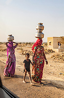 Looking through a car window two women and a child walk carrying water jugs balanced on their heads, Thar desert, outside Jaisalmer, Rajasthan, India. A man in the background watches on.
