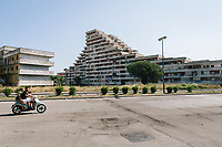 """NAPLES, ITALY - 30 JULY 2018: A view of the Vele di Scampia (English: Sails of Scampia), a large urban housing project built between 1962 and 1975 in the Scampia neighbourhood, one of the poorest and most disadvantaged in Italy, is seen here in Naples, Italy, on July 30th 2018.<br /> <br /> Thanks to Roberto Saviano's bestselling book """"Gomorrah"""" — and subsequent film and TV series — the the Vele di Scampia are known worldwide as a hotbed for drugs, prostitution and the mafia. In 2016 the city council announced an ambitious €58 million plan to tear down three of the decaying buildings and convert the fourth into offices.<br /> <br /> After the first death threats of 2006 by the Casalese clan , a cartel of the Camorra, which he denounced in his exposé and in the piazza of Casal di Principe during a demonstration in defense of legality, Roberto Saviano was put under a strict security protocol. Since 2006 Roberto Saviano has lived under police protection.<br /> <br /> Saviano's latest novel """"The Piranhas"""", which tells the story of the rise of  a paranza (or Children's gang) and it leader Nicolas, will be released in the United States on September 4th 2018."""