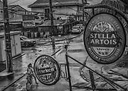 Saint-Georges de l'Oyapock, Guyane, 2015.<br /> <br /> La commune de Saint-Georges s&rsquo;&eacute;tend sur 2320 km2 et doit son origine &agrave; la cr&eacute;ation d'un bagne dont il ne reste plus de trace. Ce camp construit en 1853 pour contenir la pr&eacute;sence br&eacute;silienne est une des pires exp&eacute;riences de la d&eacute;portation guyanaise. Du fait des maladies tropicales, c&rsquo;est un des bagnes o&ugrave; la mortalit&eacute; est la plus forte. Face &agrave; l'h&eacute;catombe, on y envoie les condamn&eacute;s d'origine africaine jug&eacute;s plus r&eacute;sistants. Bien sur le taux de mortalit&eacute; ne faiblit pas et le camp est ferm&eacute; en 1863. Apr&egrave;s la d&eacute;couverte d'or en 1885, Saint-Georges se repeuple et devient un camp de base pour l&rsquo;orpaillage. La commune de Saint-Georges de l'Oyapock est officiellement cr&eacute;&eacute;e en 1946.<br /> <br /> Au d&eacute;but des ann&eacute;es 2000, Saint-Georges est un village cr&eacute;ole totalement enclav&eacute;, tourn&eacute; vers le Br&eacute;sil, accessible par une piste command&eacute;e par l&rsquo;&Eacute;tat &agrave; la l&eacute;gion et desservie par des taxis clandestins locaux, c&rsquo;est &agrave; dire br&eacute;siliens. Une liaison a&eacute;rienne irr&eacute;guli&egrave;re permet d&rsquo;effectuer les d&eacute;placements vers Cayenne, la capitale. L&rsquo;ouverture de la Route Nationale 2 permet de rallier le littoral en 3 heures depuis 2003, l'a&eacute;rodrome n'est plus utilis&eacute; que par les h&eacute;licopt&egrave;res desservant le centre de sant&eacute;. Jusque-l&agrave; tr&egrave;s isol&eacute;e, Saint-Georges a d&eacute;velopp&eacute; une strat&eacute;gie sociale, &eacute;conomique et culturelle structur&eacute;e par le fleuve, v&eacute;ritable communaut&eacute; de vie pour ses riverains qui parlent &agrave; la fois br&eacute;silien et fran&ccedil;ais, cr&eacute;ole et am&eacute;rindien.<br /> <br /> La bourgade ouvre l&rsquo;oeil deux fois par jour : quand