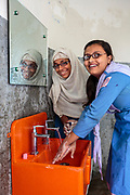 Two schoolgirls washing their hands with clean water in a Splash sink