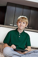 Happy young boy with tablet pc sitting on rug