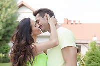 Side view of romantic young couple kissing outdoors
