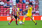 Anthony Hartigan (#8) of AFC Wimbledon runs past Charlie Wyke (#9) of Sunderland AFC during the EFL Sky Bet League 1 match between Sunderland and AFC Wimbledon at the Stadium Of Light, Sunderland, England on 24 August 2019.