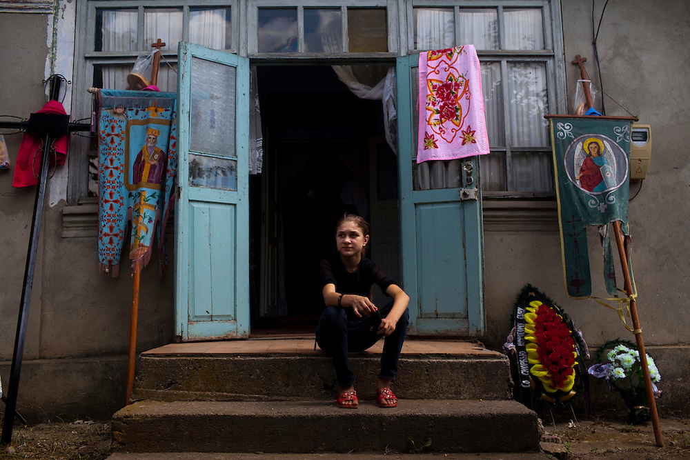 Maria Stupalov sits outside of her grandmother's home while she waits for the funeral of her father, who died of MDR-TB, to begin...