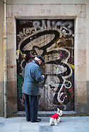 A older man with a little dog wearing a red sweater, opens his door covered in graffiti in the gothic quarter, Barcelona, Spain.