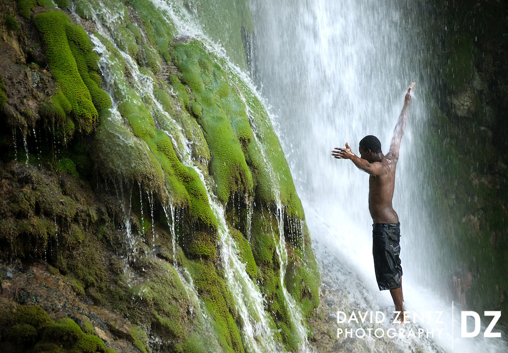A young man worships beneath the cascading falls at Saut D'eau in central Haiti during the annual voodoo festival held there each July.