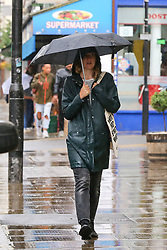 © Licensed to London News Pictures. 27/06/2020. London, UK. A woman shelters from rain an underneath umbrella in north London following a very hot week which saw highest temperature of the year so far. Photo credit: Dinendra Haria/LNP
