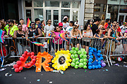 "New York, NY - 25 June 2017. New York City Heritage of Pride March filled Fifth Avenue for hours with groups from the LGBT community and it's supporters. Spectators behind a disheveled sign made of a rainbow of balloons that reads ""Proud""."