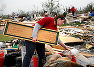 23 APRIL 2011 -- BRIDGETON, Mo. -- Tera Hockaday, a volunteer form nearby Maryland Heights, Mo., helps the family of Terry Hayes and Mary Ellen Norton-Hayes collect salvaged items in the driveway of their home on Beaverton Drive in Bridgeton, Mo. Saturday, April 23, 2011. The home was destroyed in an apparent tornado that struck the community Friday, April 22, 2011. Image © copyright 2011 Sid Hastings.
