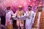Four men observe Holi festivities from the sidelines in Barsana, India. One man reads a newspaper.