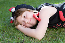 Little girl dressed as a spider sleeping,