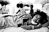 In the garden of the central hospital in Port Au Prince, is this young girl lying in a hospital bed in the open. She has pain and is still in shock 2 weeks after her world collapsed and rubble covered almost the entire city.