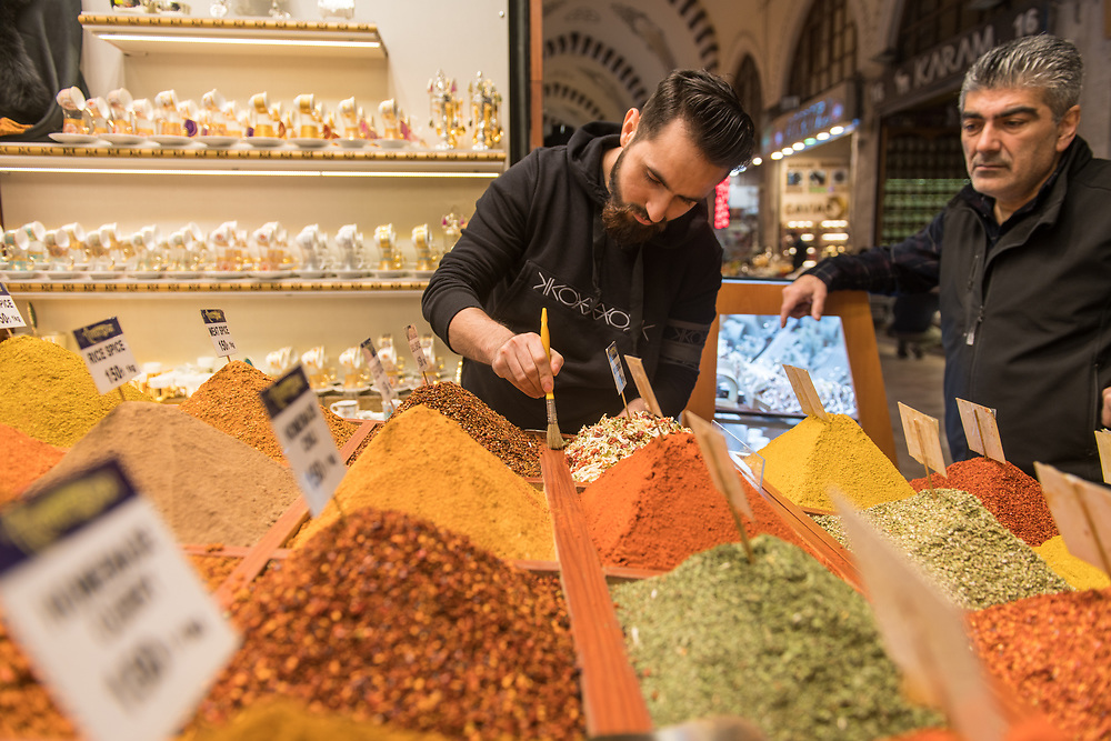 Male merchant uses paint brush to tidy up excess spices off of container as another adult male watches him at Istanbul Spice bazaar in Turkey