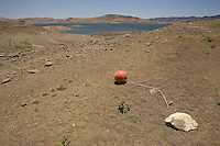 GUSTINE, CA - JULY 16:   A buoy is seen lying in the sand at the bottom of the San Luis Reservoir on July 16, 2007 in Gustine California. California Governor Arnold Schwarzenegger stressed the importance of a comprehensive water plan as the current system is not prepared to handle the population growth projected for the next 50 years. The reservoir which is filled to just 20.797 percent of capacity and is down 186 feet from normal levels supplies water for the Silicon Valley, Central Valley farms and Southern California homes and businesses.  (Photograph by David Paul Morris)