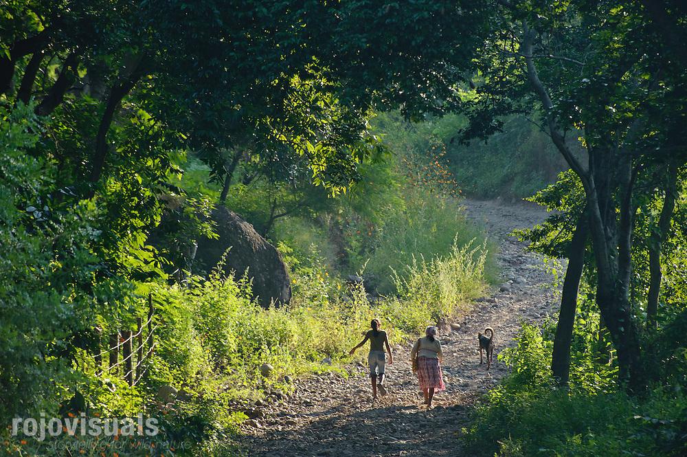 El tiempo transcurre a otro ritmo en la comunidad de El Naranjo. Una anciana y una niña wixarikas acaban de cruzar el río con su perro y emprenden el camino hacia la carretera general.