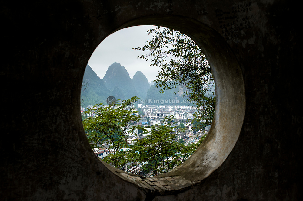 High angle view through a round window of Yangshuo, China.  The window is part of a temple that is built on a Karst formation high above the city.