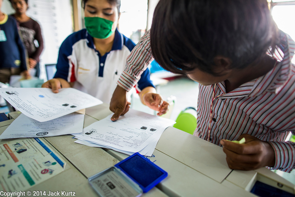 09 JULY 2014 - ARANYAPRATHET, SA KAEO, THAILAND: A Cambodian migrant worker puts his thumbprint on his ID documents at the Thai Immigration One Stop Service Center in Aranyaprathet on the Thai-Cambodian border. More than 200,000 Cambodian migrant workers, most undocumented, fled Thailand in early June fearing a crackdown by Thai authorities after a coup unseated the elected government. Employers have been unable to fill the vacancies created by the Cambodian exodus and the Thai government has allowed them to return. The Cambodian workers have to have a job and their employers have to vouch for them. The Thai government is issuing temporary ID cards to allow them to travel openly to their jobs. About 800 Cambodian workers came back to Thailand through the Aranyaprathet border crossing Wednesday. The Thai government has opening similar service centers at three other crossing points on the Thai-Cambodian border.    PHOTO BY JACK KURTZ