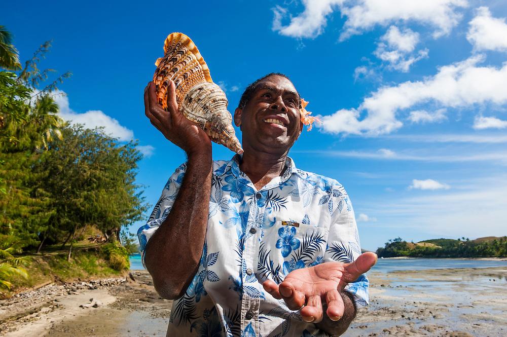 Local fijian man blowing on a huge shell, Safe Landing resort, Nacula island, Yasawas, Fiji, South Pacific