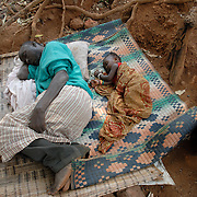 Sierra Leone .Looking Town community. Sick man and grandaughter sleeping outdoors.