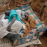Sierra Leone .Looking Town community. Sick man and grandaughter sleeping outdoors.