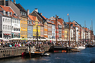 Boats and tourists on a summers day in Nyhavn, Copenhagen. The area is popular with tourists due to its picturesque setting and colourful buildings.