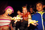 Ravers wear fluorescent  clothing with dummy, glow-in-the-dark, spikey hair and glowsticks, U.K, 1990s.