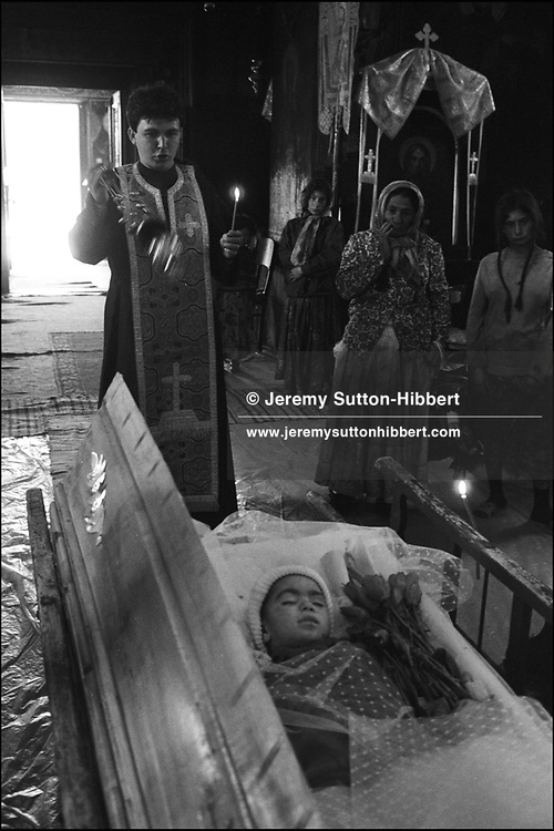 THE FUNERAL OF FOUR YEAR OLD MENINGITIS VICTIM, FLORIN MIHAI. HIS SISTER GABRIELA LOOK ON AT HIM AS HE LIES IN THE COFFIN, WEARING HIS HAT, IN THE LOCAL ROMANIAN ORTHODOX CHURCH. SINTESTI, ROMANIA, MAY 1997..©JEREMY SUTTON-HIBBERT 2000..TEL./FAX. +44-141-649-2912..TEL. +44-7831-138817.