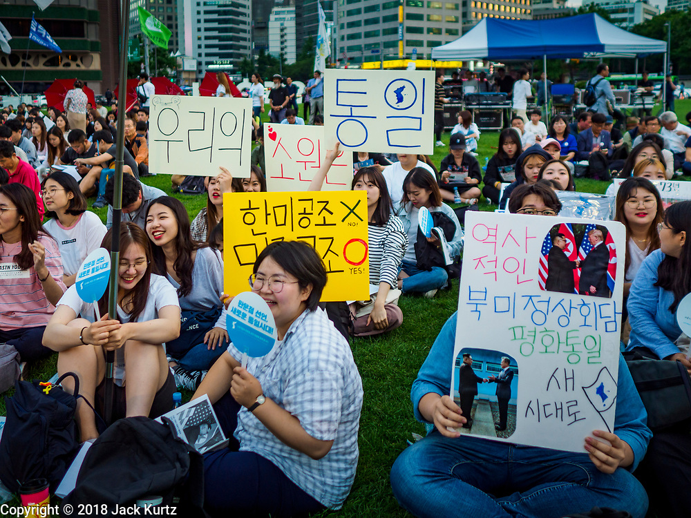"""15 JUNE 2018 - SEOUL, SOUTH KOREA:  South Koreans listen to speakers during a rally to mark the anniversary of the signing of the June 15th North–South Joint Declaration between South Korea and North Korea. The Declaration was negotiated by late South Korean President Kim Dae-jung and North Korean leader Kim Jong-il and signed on 15 June 2000. It was a part of South Korea's """"Sunshine Policy,"""" which guides the South's relationship with North Korea. This year's observance of the anniversary was bolstered by the recent thawing in relations between North Korea and South Korea and the US.     PHOTO BY JACK KURTZ"""