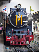 "05 DECEMBER 2013 - BANGKOK, THAILAND:  A special steam engine train leaves Hua Lamphong Train Station on the 86th birthday of Bhumibol Adulyadej, the King of Thailand. Dec. 5, the King's Birthday, is a national holiday in Thailand, and is also celebrated as the country's ""Fathers' Day."" The State Railways of Thailand put on special trains to take people to the King's ""Summer Palace"" in the oceanside community of Hua Hin where the King granted a public audience. There were also merit making ceremonies throughout the country.  Many people wear yellow on the King's Birthday because yellow is the color associated with his reign. As of 2013, he was the longest reigning monarch in the world.          PHOTO BY JACK KURTZ"