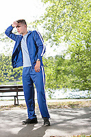Full length of tired young jogger standing on path in park