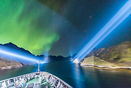 The scene as the m/s Nordlys exits the narrow Trollfjorden fjord, with the ship&rsquo;s spotlights lighting the walls of the narrow fjord and with the aurora dancing. Ahead lies the winter sky with Taurus and the Pleiades rising. This was a magical moment indeed, one of the best of the Norway cruise. <br /> <br /> This is a single 0.8 sec exposure with the 14mm Sigma Art lens at f/1.8 and Nikon D750 at ISO 6400.