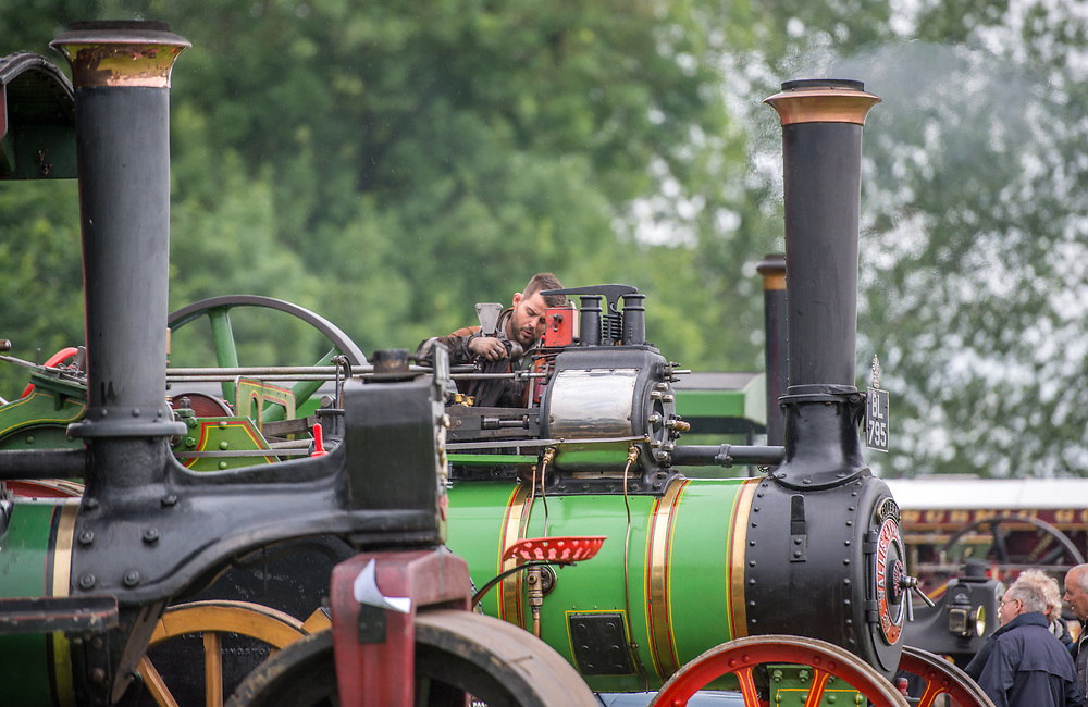 Young male uses dirty rag to polish up steam engine tractor,  Masham, North Yorkshire, UK