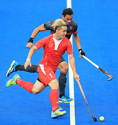 Netherlands' Glenn Schuurman (back) and China's Xiaoping Guo battle for the ball during the Men's World Hockey League match at Lee Valley Hockey Centre, London.