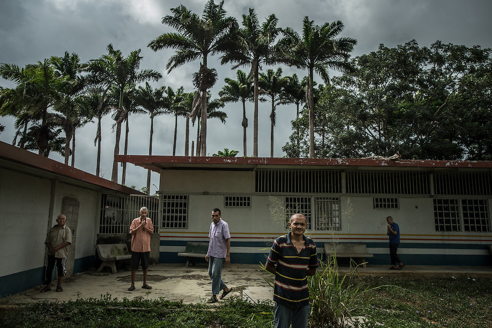 BARQUISIMETO, VENEZUELA - AUGUST 25, 2016: Patients walk around the garden of the men's ward.  The economic crisis that has left Venezuela with little hard currency has also severely affected its public health system, crippling hospitals like El Pampero Psychiatric Hospital by leaving it without the resources it needs to take care of patients living there, the majority of whom have been abandoned by their families and rely completely on the state to meet their basic needs. The hospital has not employed a psychiatrist for over two years. The halls are filled with sounds of patients crying or screaming, and an overpowering stench of urine and feces.  Drugs used to combat bipolar disorder, epilepsy, schizoaffective disorder and chronic anxiety are now in short supply, as are numerous sedatives and tranquilizers needed to care for patients. Members of the nursing staff debate daily which patients are the most unstable, to decide which patients will receive pills and which will go without. When a patient loses control, often the only thing they can do is lock them in an isolation cell to prevent them from hurting themselves, other patients and members of the staff. The hospital does not even have basic hygiene or cleaning supplies.  There is no soap, no shampoo, no tooth paste, no toilet paper.  Patients relieve themselves in the common areas and patio area, and clean themselves only with water. Nearly every patient is infected with scabies because they do not have the resources to bathe properly or to have their threadbare, misfitted clothes washed as often as needed. To make matters worse, the hospital only has running water a few hours a day.  PHOTO: Meridith Kohut for The New York Times