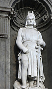 Statue of Frederick II, Holy Roman Emperor, 1194-1250, by Emanuele Caggiano, 1837-1905, on the main facade of the Palazzo Reale de Napoli, on the Piazza del Plebiscito, Naples, Campania, Italy. Beneath the statue is the excommunication bubble launched by Pope Gregory XI and a series of manuscript codes, and reference to the foundation of Studio Napoletano in 1224, now the University of Naples Federico II. The Royal Palace of Naples was a residence of the Bourbon Kings, built in the 17th and 18th centuries in Italian Baroque and Neoclassical styles. Naples is the second largest city in Italy and has been settled since the 2nd millennium BC. The historic city centre is the largest in Europe and is listed as a UNESCO World Heritage Site. Picture by Manuel Cohen