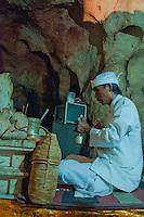 Hindu priest praying inside the cave temple complex at Goa Giri Putri on Nusa Penida, Bali, Indonesia
