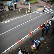 SAGAMIHARA, JAPAN - JULY 27 :  Police investigators measuring the distance of a found object dropped by the suspect in front of the entrance of Tsukui Yamayuri-en building at Sagamihara on Wednesday, July 27, 2016 in Kanagawa prefecture, Japan. Police arrested 26 year old Satoshi Uematsu after breaking inside the building facility for handicapped and killing 19 people and injuring 20 in the city of Sagamihara, west of Tokyo. (Photo: Richard Atrero de Guzman/NURPhoto)