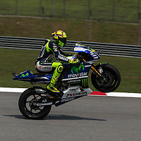 Italian MotoGP rider Valentino Rossi of Movistar Yamaha MotoGP lift his tyre at the end of qualifying session of the 2014 Malaysian Motorcycling Grand Prix in Sepang International Circuit near Kuala Lumpur, Malaysia, 25 October 2014. The Malaysian Motorcycling Grand Prix will take place from 24 to 26 October 2014.