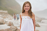 Girl (7-9) standing on beach portrait