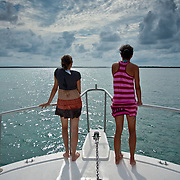 Panoramic shot shows a cloudy sky, shimmering Caribbean Sea and full length rear view of two young women on the sundeck of a dive boat in the offshore coral reef atoll, Lighthouse Reef, Belize