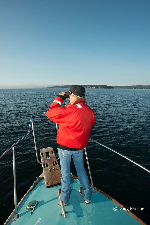 research intern Johanna Anderson scans the Bay of Fundy for North Atlantic right whales on the New England Aquarium research vessel Nereid in Grand Manan Basin, Bay of Fundy ( North Atlantic Ocean ), New Brunswick, Canada