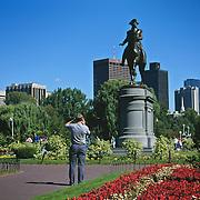 Massachusetts, Boston; Tourists Photograph George Washington Monument; Boston Common; City Skyline In Background
