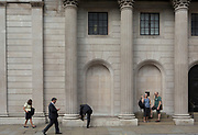 "Londoners walk, tie a loose lace and stand beneath the columns and pillars of the Bank of England on Threadneedle Street in the City of London - the capital's financial district, on 3rd September 2018, in London England. The Bank of England, is the central bank of the United Kingdom and the model on which most modern central banks have been based. Established in 1694, it is the second oldest central bank in the world. Sir Herbert Baker's rebuilding of the Bank, demolishing most of Sir John Soane's earlier building, was described by architectural historian Nikolaus Pevsner as ""the greatest architectural crime, in the City of London, of the twentieth century""."