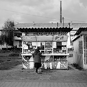 A lady shops at a small 'American fast food' kiosk situated on the main road running through the small Romanian town of  Copsa Mica, Transylvania, Romania. Copsa Mica was once described as the most polluted town in Europe. May 9, 2008  Photo Tim Clayton...Copsa Mica, a small industrial town deep in Transylvania, Romania, was described during the 1990s as the most polluted town in Europe with lead levels reaching were more than 1000 times the allowable International limits and life expectancy nine years shorter than the National average...The pollution was caused entirely by two factories, Carbosin produced black for dies and tires and closed in 1993 while Sometra, a nonferrous smelter is still operational today...The pollution was so bad sheep were black, covered in soot and health officials advised against eating livestock or vegetables and drinking the water or milk...The Communist rule of Nicolae Ceausescu is blamed for the widespread environmental degradation that left industrial parts of Romania in ecological disaster. Industry was situated in a way to concentrate pollution in small areas leaving the rest of the country relatively free of pollution. Copsa Mica in particular was left an environmental disaster...The pollution caused a direct affect on human health with widespread Lung disease, Impotency, the highest infant mortality rate in Europe, Lead poisoning and behavioral problems...Fifteen years on since the closure of Carbosin in 1993, the factory skeleton remains as part of the towns bleak landscape, Unfinished communist style housing blocks still stand in the heart of the towns housing estate. The town's inhabitants are still trying to recover from the long lasting effects of pollution...Recent survey's found the soil contained so much lead that it was 92 times above the permitted level; the vegetation had a lead content 22 times above the permitted level. While toxins have penetrated at least one meter (three feet) into the soil lea