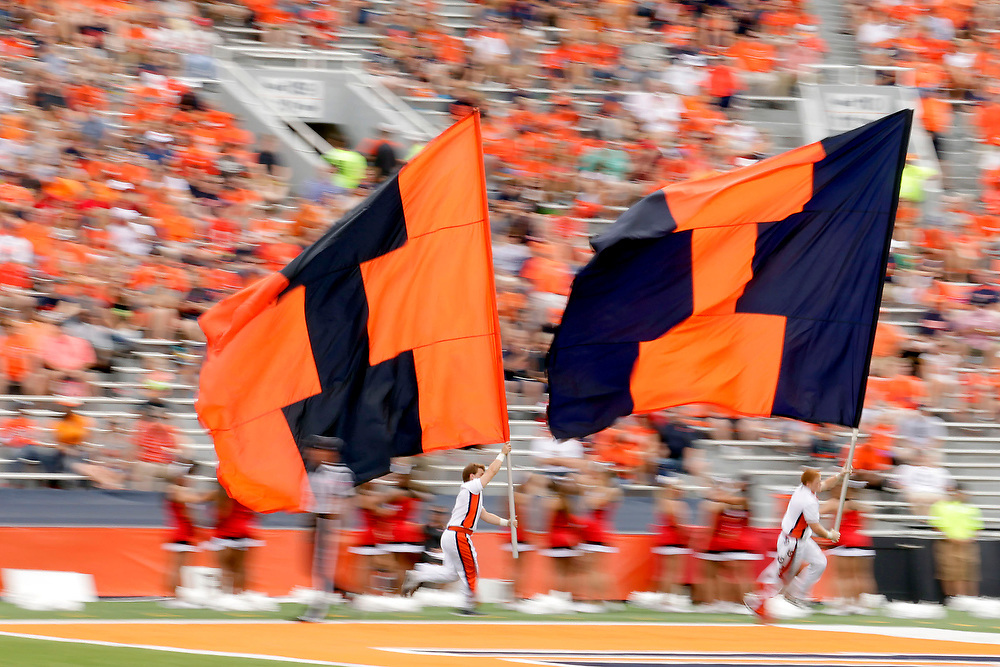 Cheerleaders run along the sideline with flags during the first half of an NCAA college football game against Youngstown State at Memorial Stadium Saturday, Aug. 30, 2014, on the University of Illinois campus in Champaign, Ill. (Lee News Service/ Stephen Haas)